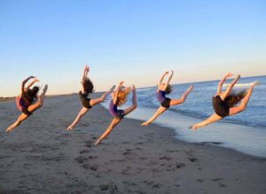 about us - photo of girls dancing on the beach